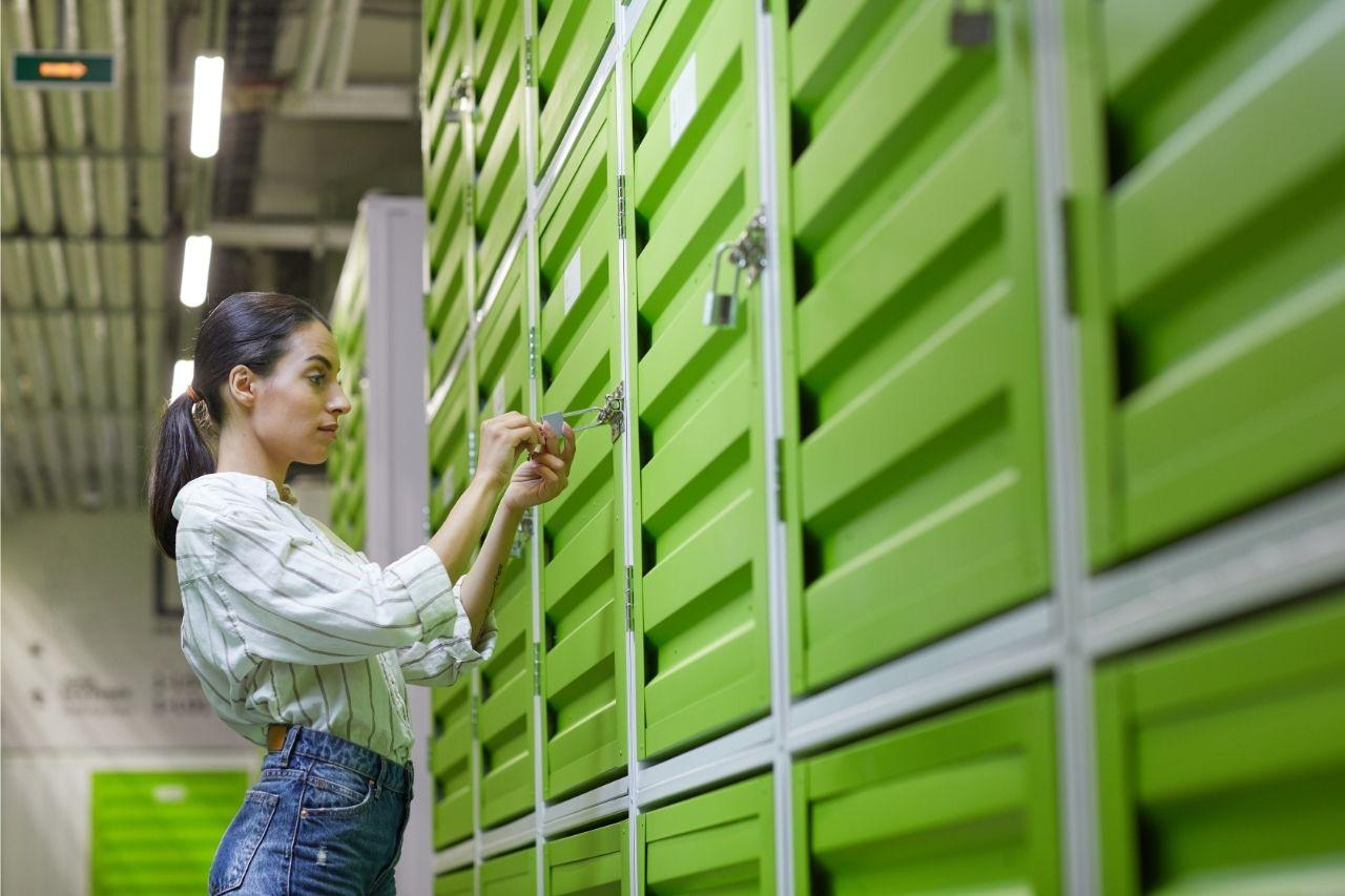 Na foto, uma mulher trancando o seu compartimento de self storage